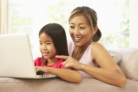 Mother And Daughter Using Laptop At Home photo