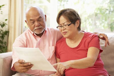 Senior Couple Discussing Document At Home photo