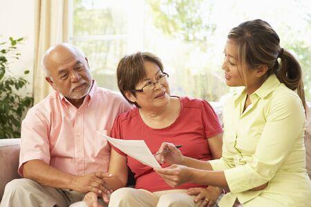 Senior Couple Talking To Financial Advisor At Home Stock Photo - 6135233