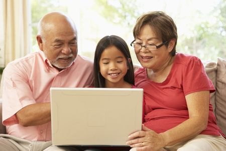 grandkids: Grandparents And Grandaughter Using Laptop Computer At Home Stock Photo