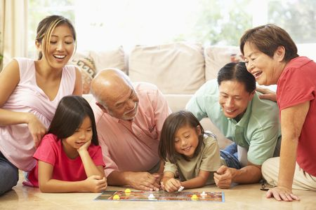 happy asian family: Extended Family Group Playing Board Game At Home Stock Photo