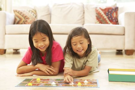 ni�as jugando: Dos chicas Roll Board Game At Home