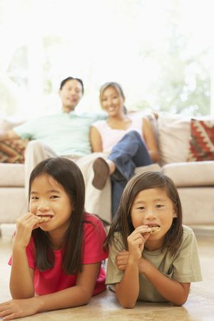 Two Girls Eating Cookies At Home photo