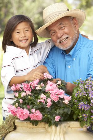 Grandfather And Granddaughter Gardening Together photo