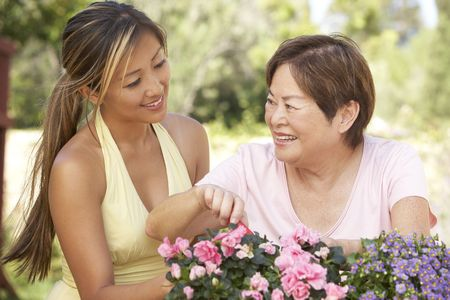Mother With Adult Daughter Gardening Together photo