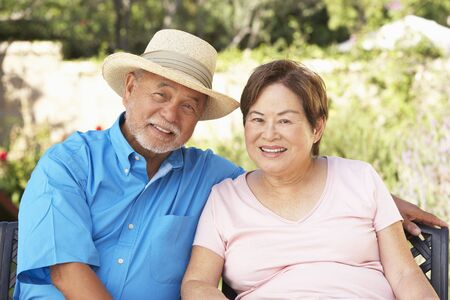 70s adult: Senior Couple Relaxing In Garden Together Stock Photo