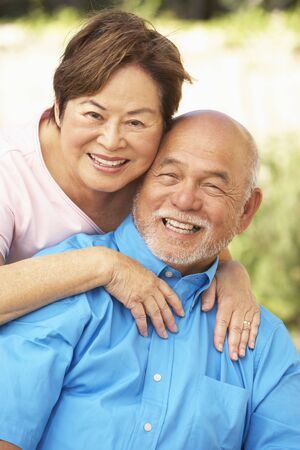 happy asian couple: Senior Couple Relaxing In Garden Together Stock Photo