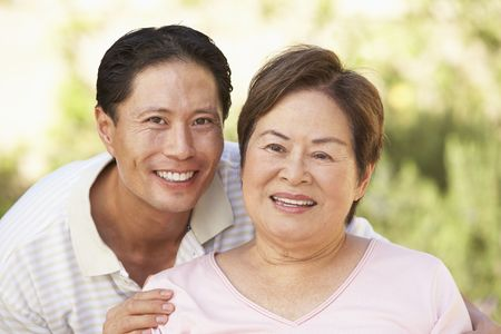 mother on bench: Senior Woman With Adult Son In Garden Stock Photo