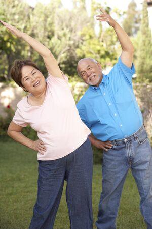 men exercising: Senior pareja ejerciendo en el jard�n