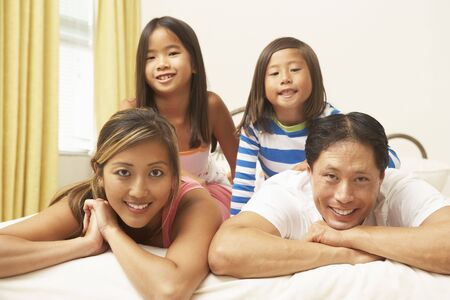 Young Family Relaxing In Bedroom photo