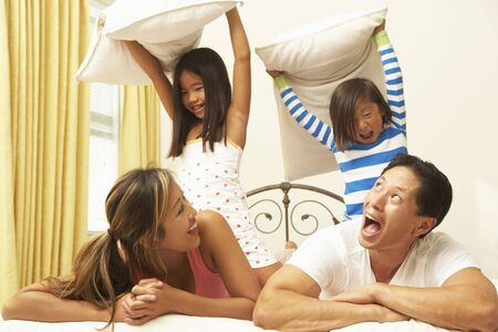 Young Family Having Pillow Fight In Bedroom photo
