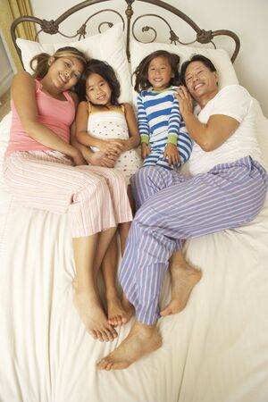 Young Family Relaxing In Bedroom Stock Photo - 6128084