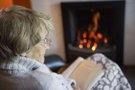 mujer leyendo libro: Libros de lectura de mujer Senior por incendio en casa Foto de archivo