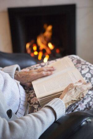 mujer leyendo libro: Detalle de los libros de lectura de mujer Senior por incendio en casa