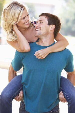 Young Man Giving Woman Piggyback Outdoors Stock Photo - 6142861