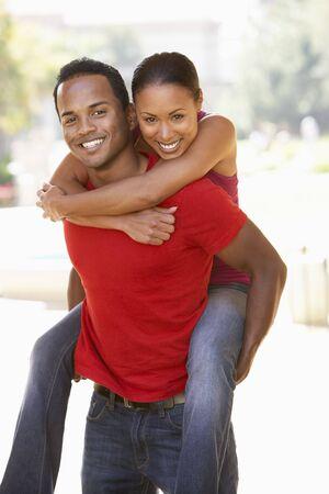 Young Man Giving Woman Piggyback Outdoors Reklamní fotografie