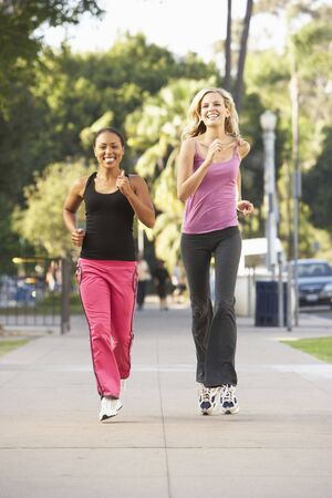 Two Female Friends Jogging On Street photo
