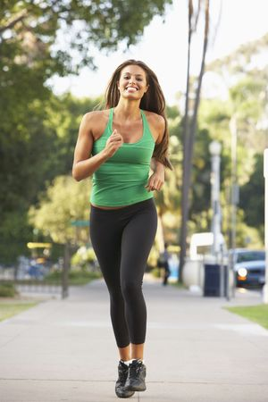 woman running: Young Woman Jogging On Street Stock Photo