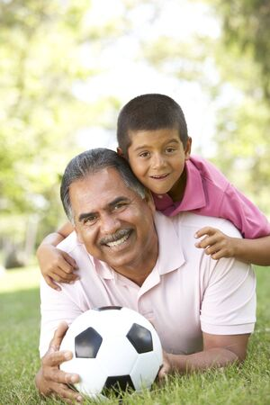 sons and grandsons: Grandfather With Grandson In Park With Football Stock Photo
