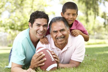 sons and grandsons: Grandfather With Son And Grandson In Park With American Football