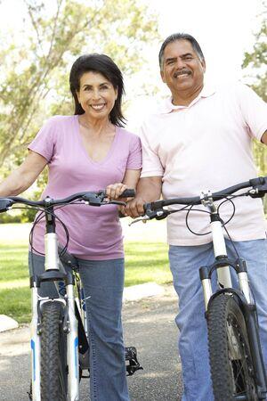 hispanic women: Senior Couple Riding Bikes In Park