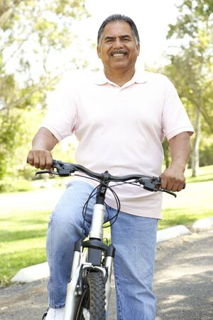 Senior Man Riding Bike In Park photo
