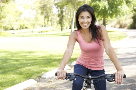 Young Woman Riding Bike In Park Stock Photo - 6135778