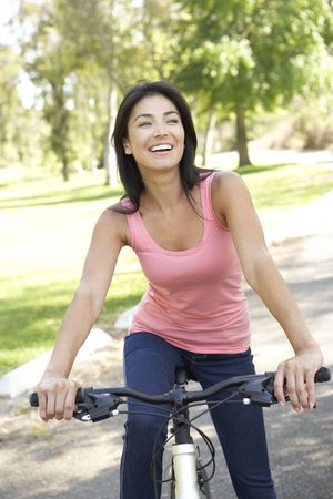 Young Woman Riding Bike In Park Stock Photo - 6128048