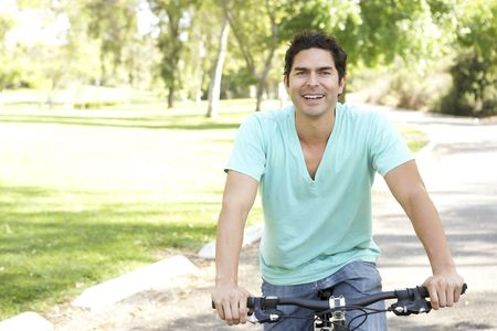 Young Man Riding Bike In Park Stock Photo - 6135705