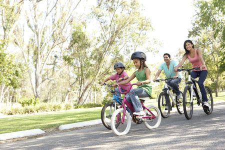 hispanic women: Young Family Riding Bikes In Park