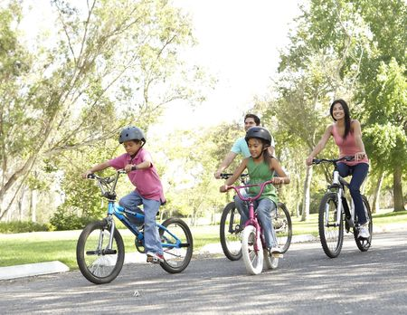 Young Family Riding Bikes In Park photo