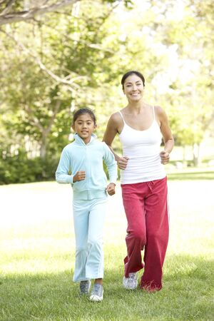Mother And Daughter Exercising In Park photo