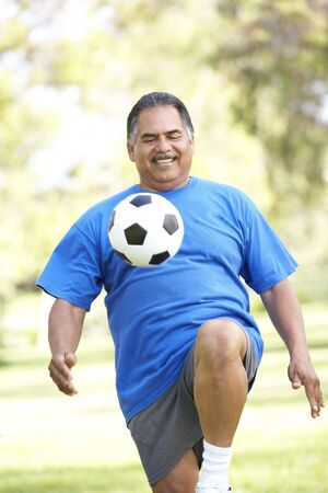 active senior: Senior Man Exercising With Football In Park