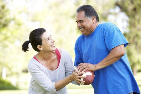 enjoy space: Senior Couple Exercising With American Football In Park Stock Photo