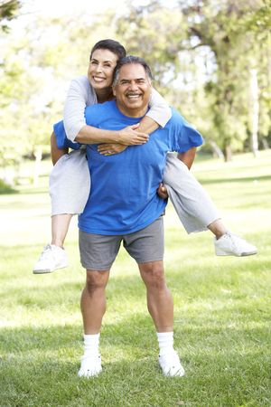 active couple: Senior Couple In Sports Clothing Having Fun In Park Stock Photo