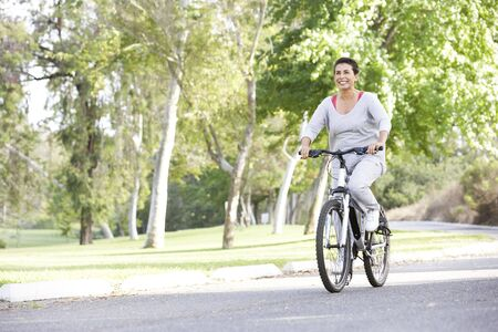 Senior Woman Cycling In Park photo