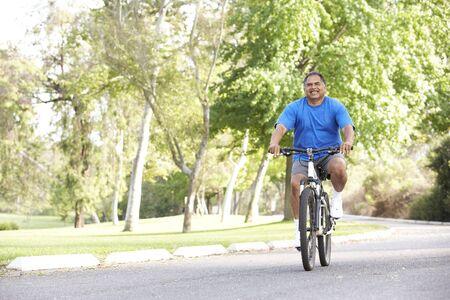 Senior Man Cycling In Park photo