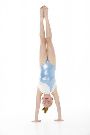 7 year old girl: Studio Portrait Of Young Female Gymnast Doing Handstand Stock Photo