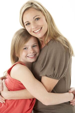 cuddling: Studio Portrait Of Mother Hugging Young Daughter Stock Photo