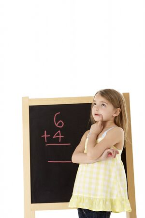 Young Girl Looking Thoughtful Next To Blackboard photo
