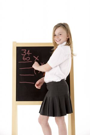 Thoughtful Female Student Wearing Uniform Next To Blackboard photo