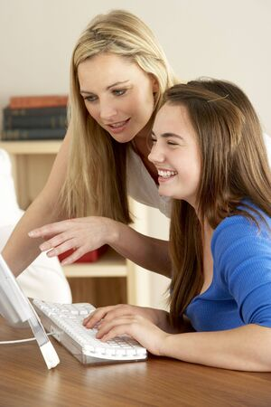 Mother And Teenage Daughter At Home Using Computer photo