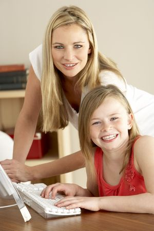 Mother And Daughter At Home Using Computer photo
