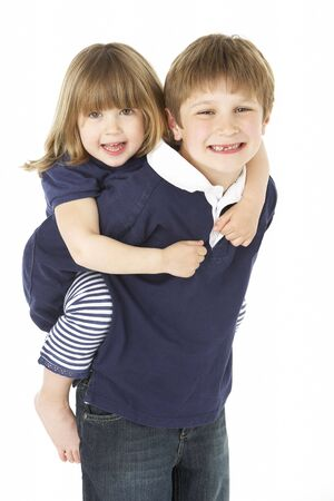 Studio Portrait Of Brother Giving Sister Piggy Back photo