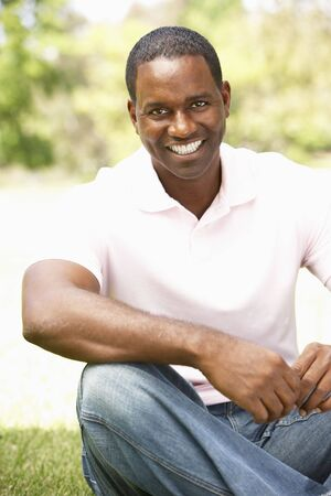 male age 40's: Portrait Of Young Man Sitting In Park Stock Photo