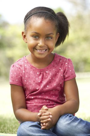 Portrait Of Young Girl Sitting In Park photo