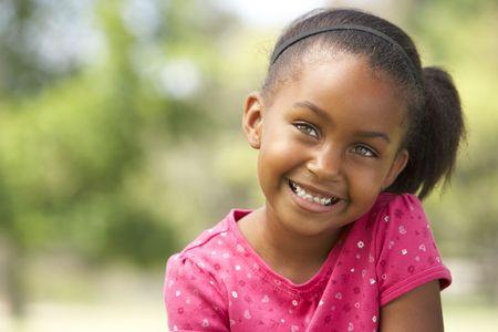 enfants qui rient: Portrait de jeune fille assise dans le parc Banque d'images