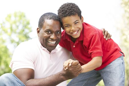 children laughing: Portrait Of Father And Son In Park