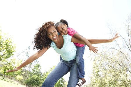 piggyback: Portrait of Happy Mother and Daughter In Park