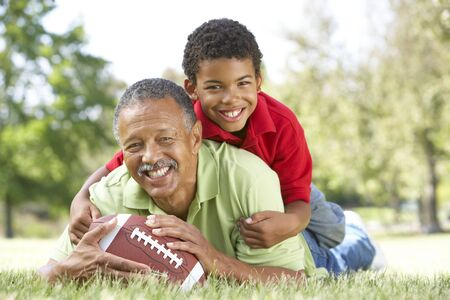 внук: Grandfather With Grandson In Park With American Football Фото со стока